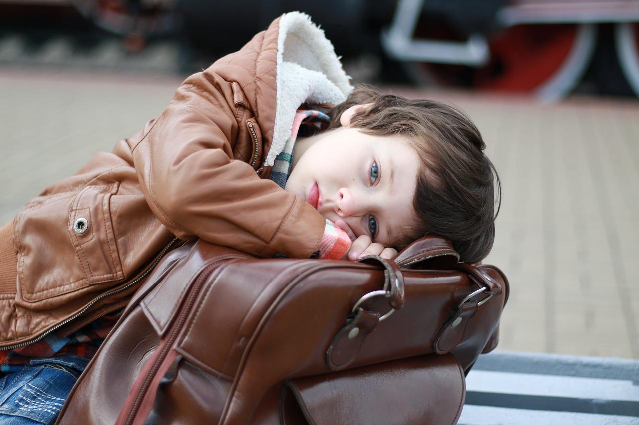 мальчик положил голову на чемодан