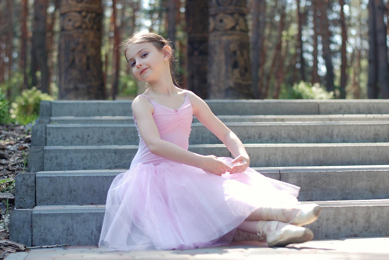 маленькая балерина сидит на ступеньках в лесу